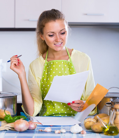 freelancer: Portrait of young european female freelancer with documents at kitchen table Stock Photo