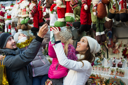 Happy family of four buying handmade decorations at Christmas market. Focus on woman Stock Photo