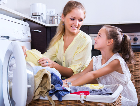 doing chores: Blonde housewife and little girl doing laundry together