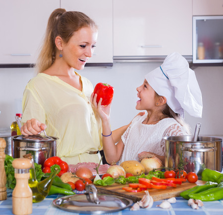 vegeterian: young russian mom and little daughter cooking vegeterian dish indoors