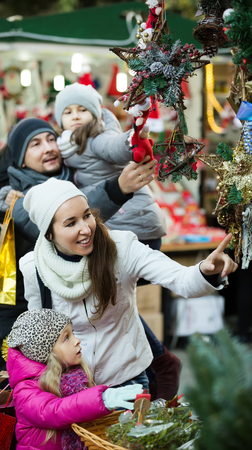 Happy family of four choosing x-mas decorations at market together. Focus on woman and girl Stock Photo