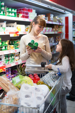ordinary woman: Smiling ordinary woman with little daughter buying sweet yoghurts in dairy section Stock Photo