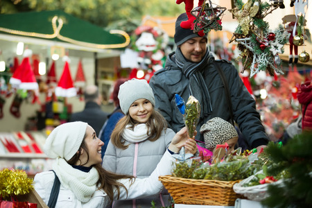Happy family of four choosing x-mas decorations at market. Focus on woman and girl