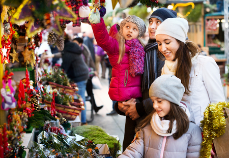 Ordinary family with little girls standing at the coniferous souvenirs counter. Focus on women