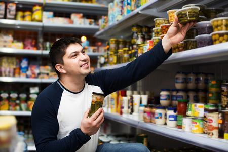 clase media: chico de clase media ordinaria choosing comida enlatada en el supermercado Foto de archivo