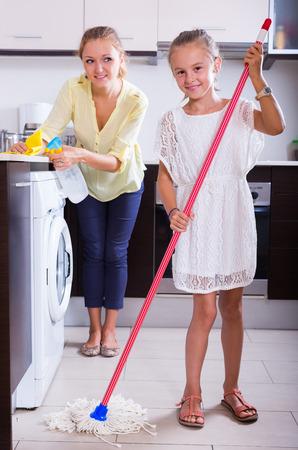 diligente: ni�a diligente ayudar a la madre sonriente alegre a limpiar en la cocina en el hogar