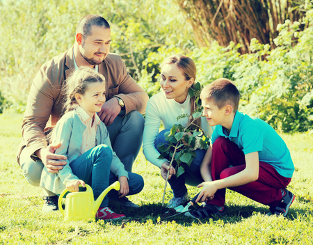 Cheerful young parents with two smiling children planting a tree together Stock Photo