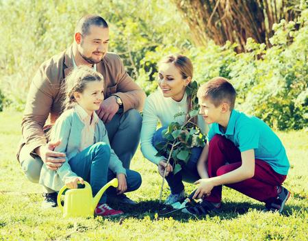 actividades recreativas: los padres jóvenes alegres con dos niños sonrientes plantar un árbol en conjunto