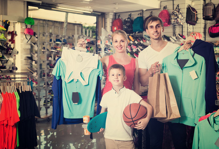 russian man: smiling young russian man and woman with boy choosing t-shirts and other goods in sport shop. focus on boy
