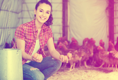 henhouse: Portrait of young european woman farmer holding fresh eggs in hands in henhouse Stock Photo