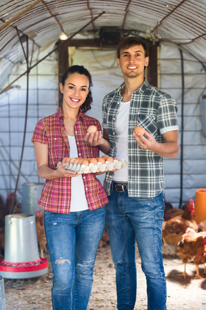 henhouse: Portrait of young man and woman farmer holding fresh eggs in carton in henhouse Stock Photo