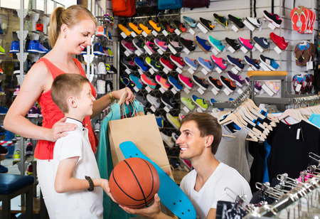 russian man: smiling young russian  man and woman buying skateboard for son in sport shop Stock Photo