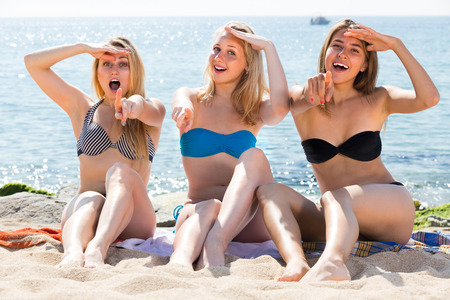 three happy smiling girls in bikini relaxing on sandy beach on hot summer day