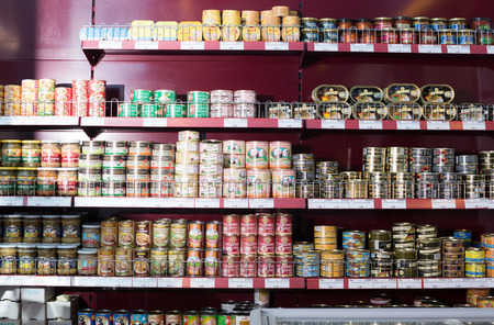 european food: BARCELONA, SPAIN - FEBRUARY 02, 2016: Shelves with ordinary assortment of canned meat and fish products in East European food store