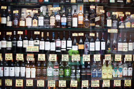 beverage display: BARCELONA, SPAIN - OCTOBER 27, 2015: View at glass display of ordinary liquor store with alcoholic beverages in bottles