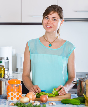 householder: Adult girl standing at a kitchen table with casserole and vegetables Stock Photo
