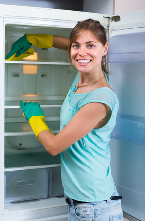 householder: Smiling girl wiping fridge parts at kitchen with lint-free rag