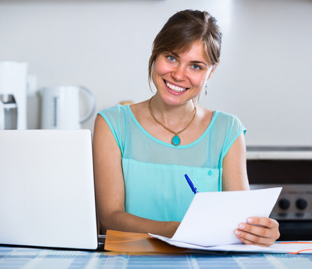 householder: Young smiling woman filling banking documents at the kitchen Stock Photo