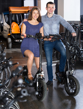 rental agency: Happy young couple selecting the bikes in a rental agency indoors. Focus on both persons Stock Photo