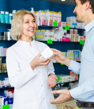 25s: female pharmaceutist in drugstore helping customer 25s to choose medication