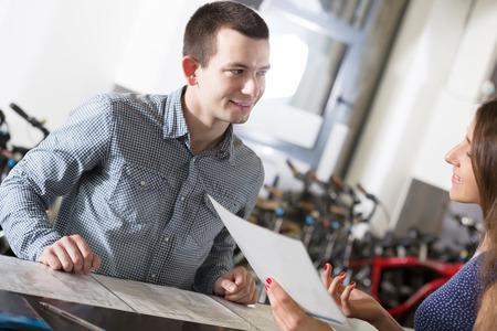 rental agency: russian female employee helping adult guy to select bike at rental agency