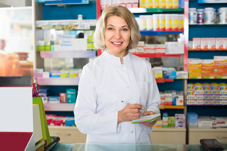 druggist: Smiling mature female technician working in chemist shop