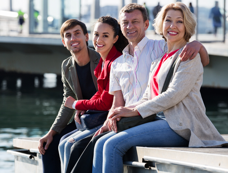Close up of happy tourists relaxing on sea front in autumn. Focus on mature man Stock Photo