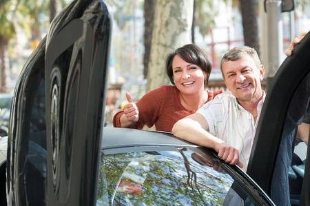 peep out: Happy mature man and woman standing near twizy electric outdoors Stock Photo