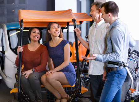 rental agency: Friendly kindly male employee helping family to select tour electrics at rental agency Stock Photo