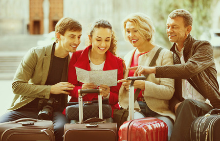 Family of four with luggage checking direction in map outdoor Stock Photo
