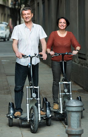 Positive man and woman 45-55 years old traveling through city by bicycles