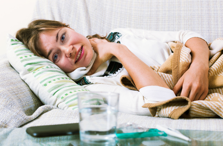 megrim: Young unhappy woman having heavy sickly quinsy in domestic interior