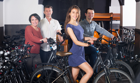 rental agency: Kindly male employee helping family to select bikes at rental agency Stock Photo