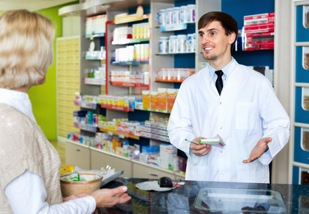 farmacy: Experienced pharmacist counseling female customer in modern farmacy