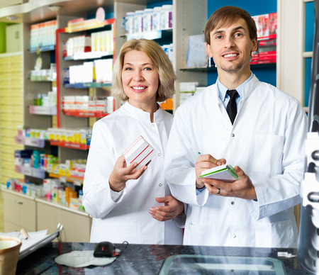 Portrait of two friendly pleasant  pharmacists working in modern farmacy Stock Photo