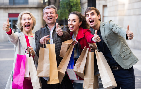 Portrait of cheerful smiling young and mature couple posing with shopping bags outdoors