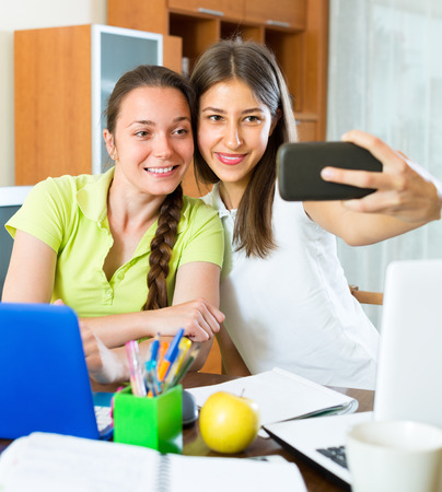 avocation: Portrait of two happy young girls doing selfie with smartphone at home Stock Photo