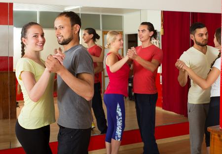 Lächelnde Erwachsene tanzen bachata zusammen im Tanzstudio Standard-Bild