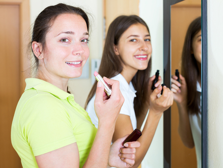 makeups: beautiful smiling woman making make-up near mirror. Focus on the left woman