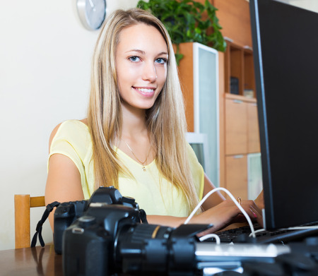 photocamera: Smiling girl working with laptop and photocamera