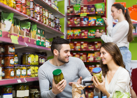canned goods: Smiling adults people standing near shelves with canned goods at shop