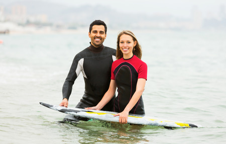waist deep: Young surfers couple waist deep in water Stock Photo