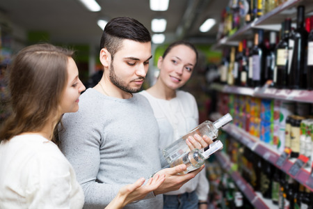 vodka bottle: Young people standing at alcohol section and checking vodka bottle. Focus on guy
