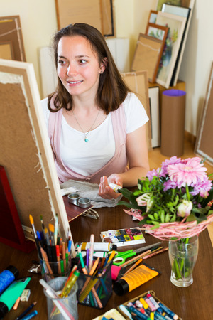 contentedness: Smiling young artist in the process of creating a new picture