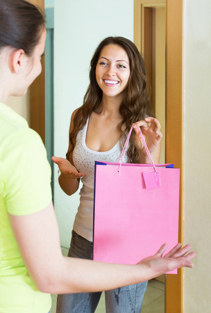 cognate: Happy young girl visiting her girlfriend with gift