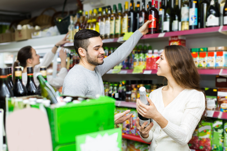 people buying: Positive adult people buying beverages for dinner at food shop
