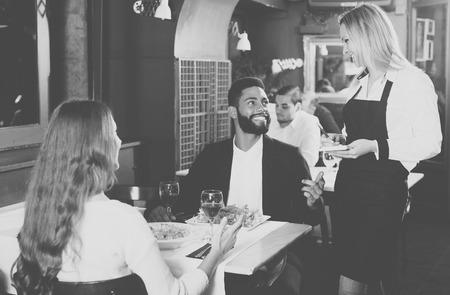 middle class: cónyuges de jóvenes felices tienen fecha en el restaurante de clase media. Centrarse en la niña rubia