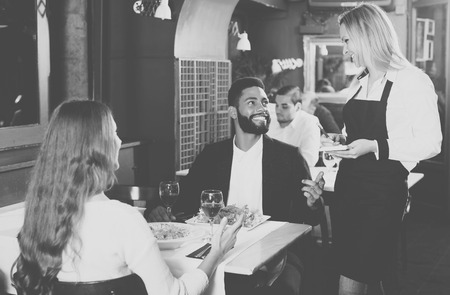 middle class: Happy young spouses having date in middle class restaurant. Focus on blonde girl Stock Photo