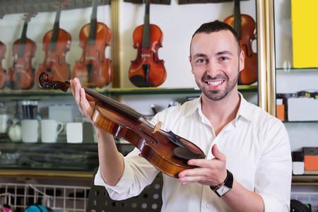 violins: Young cheerful man with beard purchasing traditional violins in store Stock Photo