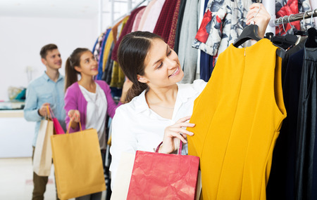 liked: Cheerful young female shopper chooses liked things in the boutique